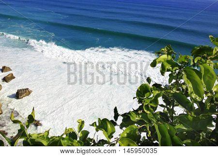 rocky sea shore covered with white foam