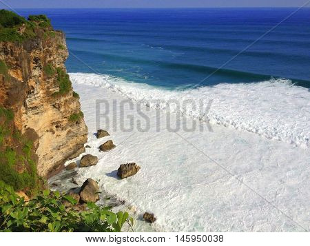 rocky sea shore covered with white foam from waves