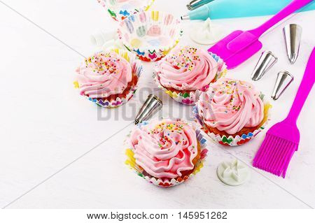 Decorated birthday cupcakes and cookware background. Birthday cupcake with pink whipped cream. Homemade party cupcakes.