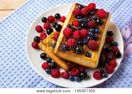 Breakfast waffles with fresh berries on the blue linen napkin. Soft Belgian waffles with blueberry raspberry and blackcurrant.