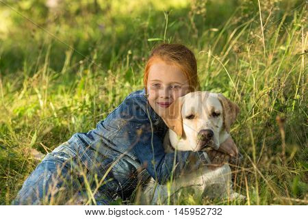 A little girl lies in the grass with his dog.