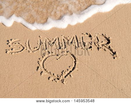 Finger drawn Summer word and Heart sign on beach sand