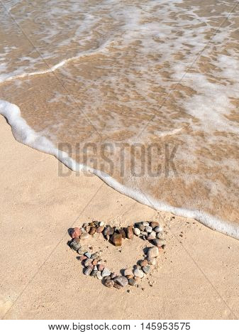 Heart sign arranged from pebbles on beach sand