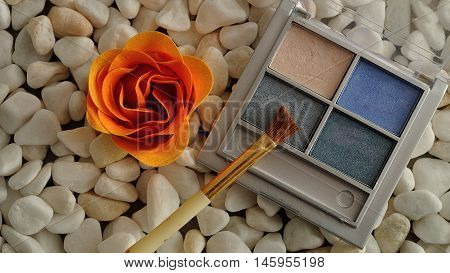 A palette with blue shades of eye shadow and a brush displayed on white pebbles with an orange flower