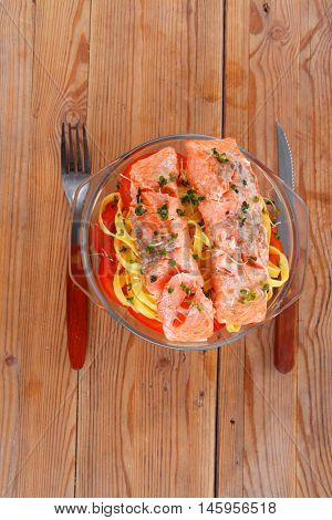 fresh fried natural pink salmon on italian traditional tagliatelles backed with tomato and vegetables served over wooden table with cutlery