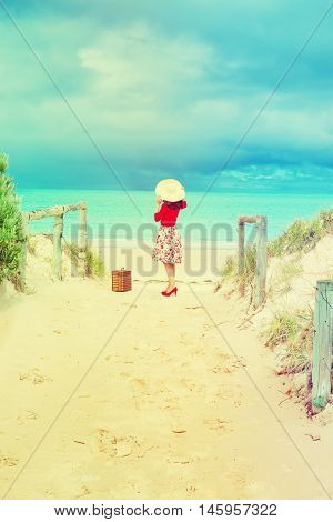 Beautiful lady in red traveler with wicker suitcase on the beach in retro style