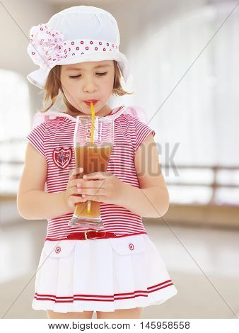 Cute little girl in pink sea dress and white hat with a large bow. Girl drinking through a straw apple juice from a large glass.On the background of the hall with a large arched window , the concept of learning and child development.