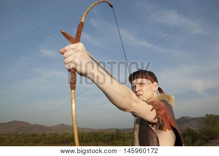 Young archer in vintage clothes with arrow and long bow