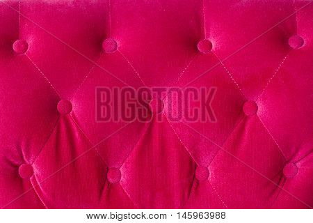 Red velvet couch background texture with sunken buttons