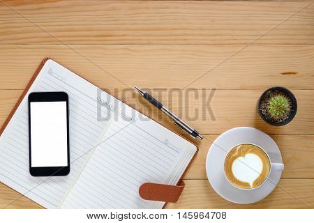Office desk table with blank screen smartphone blank page notebookpenand cup of coffee .Top view with copy space.Office desk table concept.Office supplies and gadgets on desk table.
