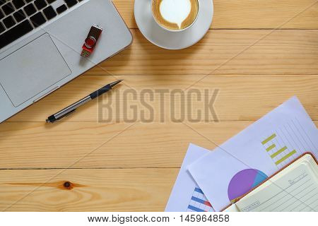 Office desk table with laptoppenanalysis chart leather notebook flat drive and cup of coffee .Top view with copy space.Office desk table concept.Office supplies and gadgets on desk table.