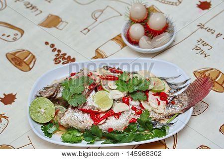 Tilapia fish streamed lemon with fruit.Selective focus.