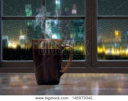 A mug with a hot drink - tea or coffee on the window sill of the window. Outside the night the city lights rain drops on the glass