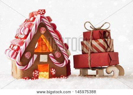 Gingerbread House In Snow As Christmas Decoration. Candlelight For Romantic Atmosphere With Snowflakes. Sled With Gifts Or Presents