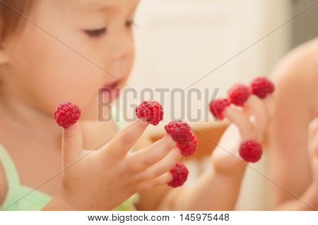 Little Child With Raspberry On Fingers