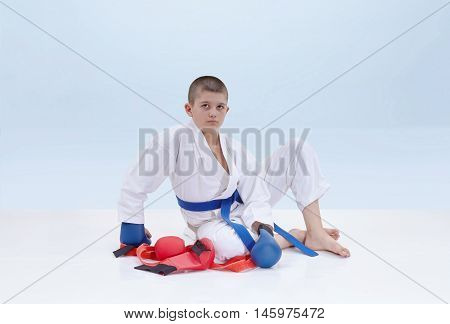On a light background karate athlete sits near a karate outfit