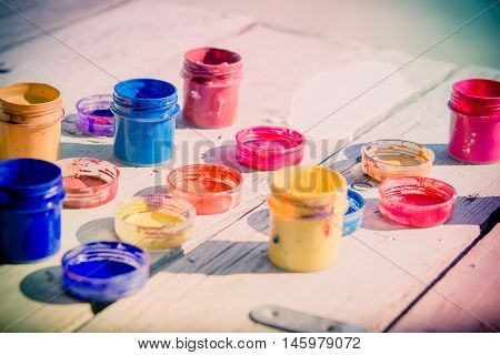 small gouache paint cans stand on a wooden table