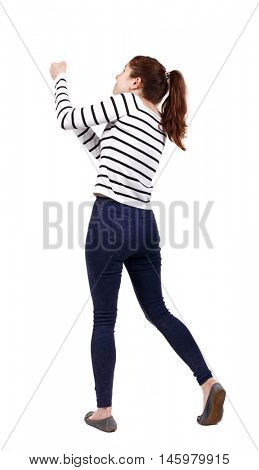 back view of standing girl pulling a rope from the top or cling to something. girl watching. girl in a striped sweater, pulling a rope from the top.