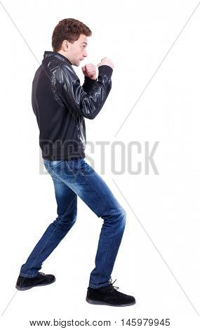 back view of guy funny fights waving his arms and legs. Curly guy in a black leather jacket in a fight.