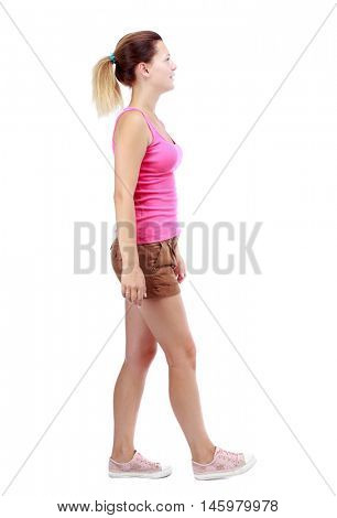 back view of walking woman. beautiful blonde girl in motion. Isolated over white background. Sport blond in brown shorts walks past the camera