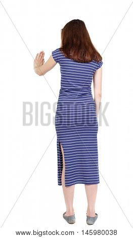 back view of woman. Young woman presses down on something. The brunette in a blue striped dress standing back hand presses the button.