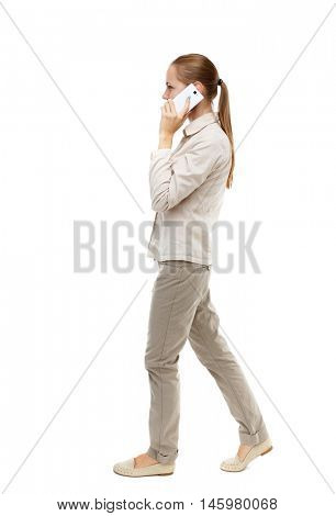 side view of a woman walking with a mobile phone. back view ofgirl in motion. Isolated over white background. Skinny girl in white denim suit talking on the phone while walking.