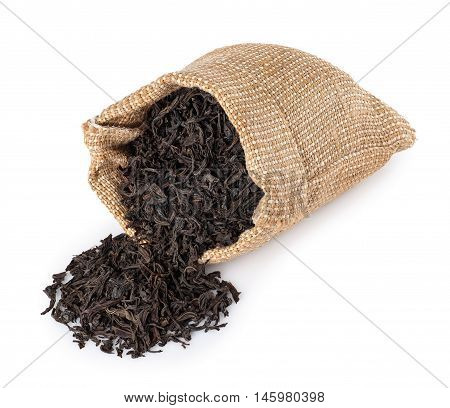 Black tea scattered of burlap bag isolated on white background. Black tea. Dry leaves of tea scattered of sack isolated on white. Dry leaves of tea
