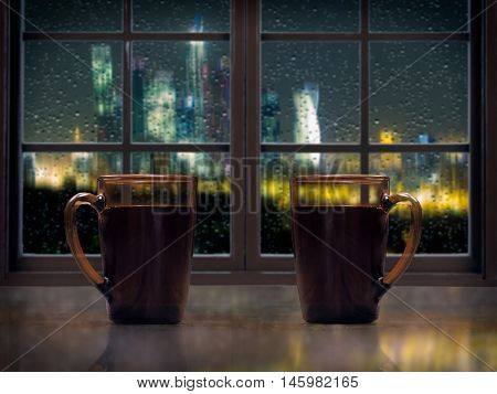 Two mugs with a hot drink - tea or coffee on the window sill of the window. Outside the night the city lights rain drops on the glass