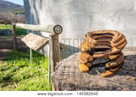A stack of horse shoes lie outside the stables on a big wooden log.