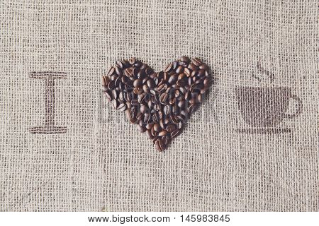 I love coffee. Burlap texture with coffee beans heart shape background, love symbol with cup. Sack cloth canvas and seeds at hessian textile
