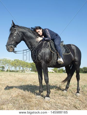young girl riding a black stallion in a field