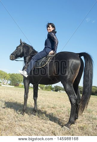 beautiful girl riding a black stallion in a field
