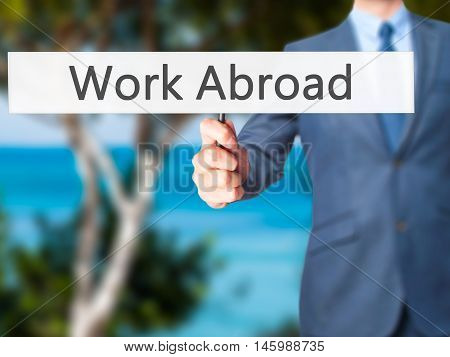 Work Abroad - Businessman Hand Holding Sign
