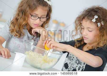 Two little girls preparing a cake mix