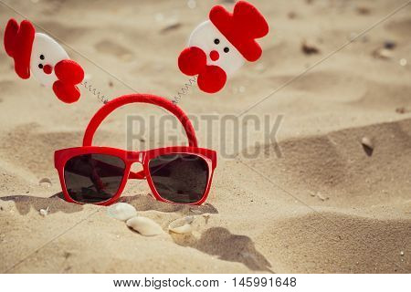 Funny christmas scene with red sunglasses on the beach. Vacation theme concept