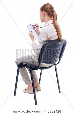 back view of young beautiful woman sitting on chair and takes notes in a notebook. Isolated over white background. Skinny girl in white denim suit thoughtfully sidit on a chair taking notes in a