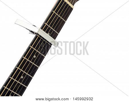 Silver capo on guitar fingerboard white background close up