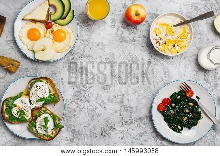 Frame of fried egg poached eggs avocado apple spinach salad muesli milk cheese sandwiches and orange juice on light surface top view