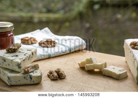 Several pieces of brie and roquefort cheese with nuts and jam