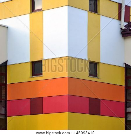 Grodno, Belarus - July 31, 2016: Geometric architectural composition. Corner of a modern building of rectangular panels of orange pink yellow and white colors. Symmetrical view.