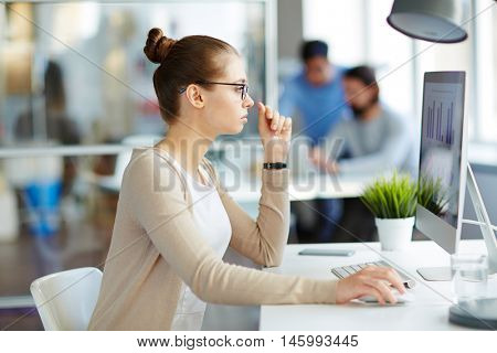 Young female marketing professional sitting at desktop computer in modern office space looking at research results and investigating business performance