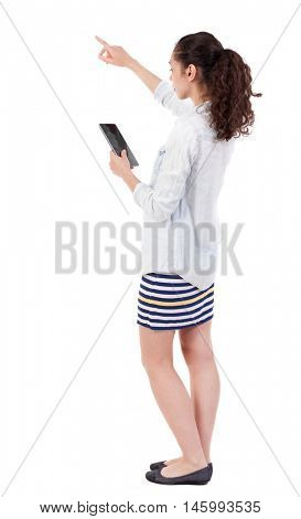 back view of pointing young beautiful  girl with tablet computer. girl  watching. Rear view people collection.  backside view of person.  Isolated over white background. Curly girl pointing to an