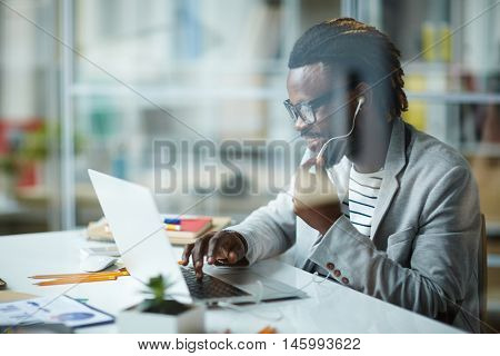 Modern young African-American entrepreneur working at successful start-up business in small office, talking with partners using phone headset and laptop, behind glass wall shot