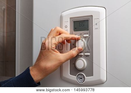 Men hand regulate temperature on 65 degree in control panel of central heating.
