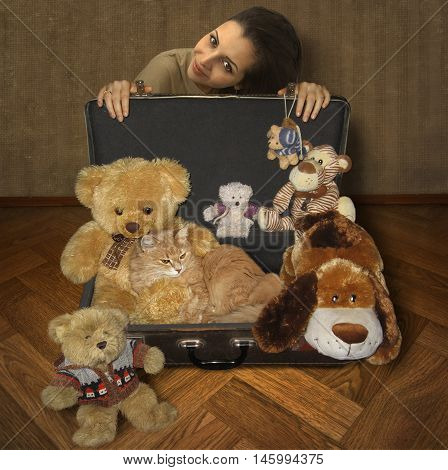 A girl is sitting next to an old open suitcase. It is filled with soft toys. Her favorite cat is lying among these toys. It looks like a toy.