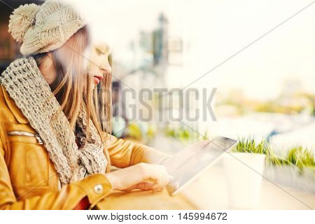Side view of young attractive girl wearing knitted hat and scarf sitting by window in cafe with tablet, surfing net, checking mail and social media, copy space to the right