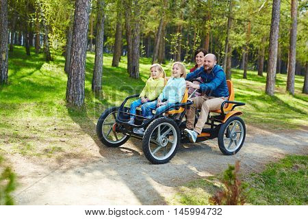 Active family with kids, mother father and two daughters, enjoying ride in four wheeled bicycle car around green forest during weekend entertainment in park