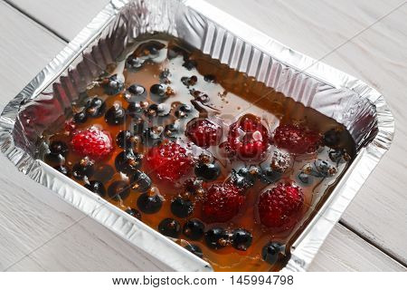 Healthy dessert. Sweet berry jelly closeup in foil delivery box. Vegetarian diet. Healthy food take away, natural organic vegan jelly from agar with raspberry and black currant