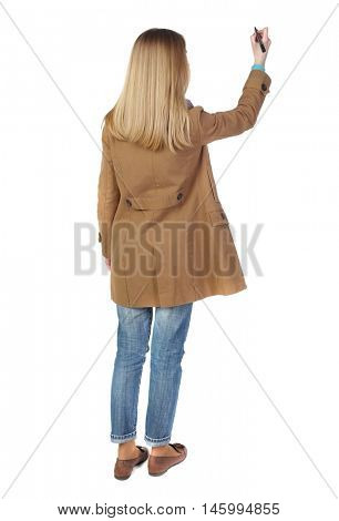 back view of writing beautiful woman. blonde in a brown cloak draws felt-tip pen on the board.