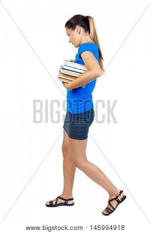Girl comes with stack of books. side view. girl in a short skirt and a blue T-shirt goes to the side with books and looking down.